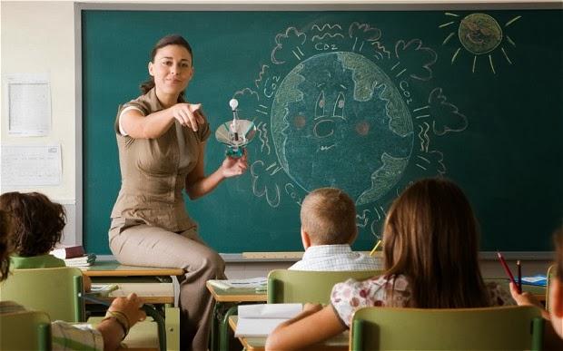 profesora explicando con una pizarra en el que está dibujada el planeta tierra