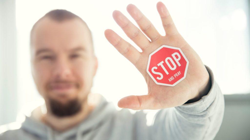 persona mostrando la palma de la mano, donde pone stop