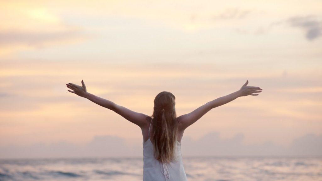 una mujer mirando al horizonte con los brazos abiertos