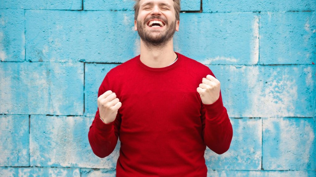 un hombre sonriendo y con los brazos indicando que ha conseguido algo