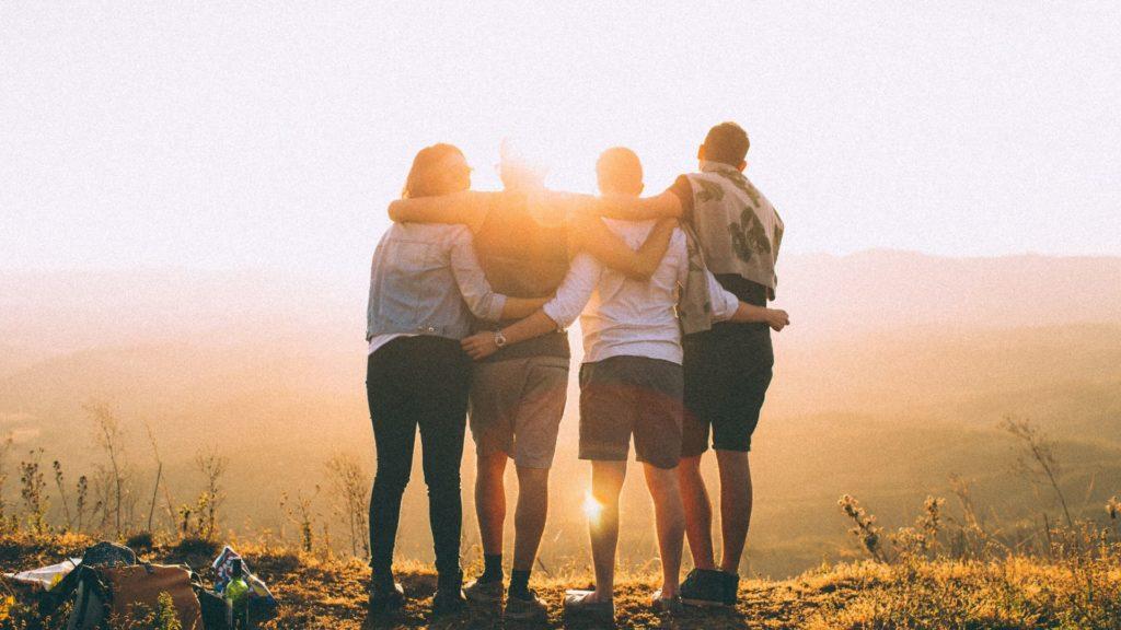 grupo de jóvenes abrazándose con el sol de fondo
