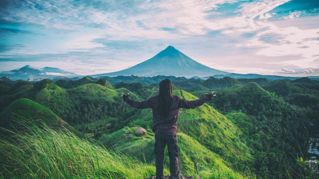 persona mirando un paisaje verde con una gran montaña al fondo